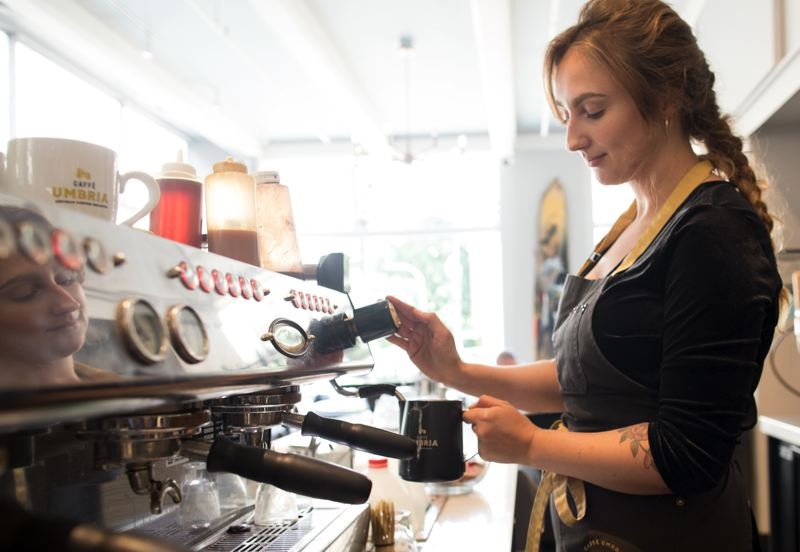 PMG PHOTO: JAIME VALDEZ - Barista Rose Sherman makes coffee for customers at Caffe Umbria in downtown Portland. The owner has put wages up in line with the new state minimum, which went to $12.50 in Portland on July, 2019, but is holding back on increasing food and drink prices.  Workers like Sherman at Caffe Umbria usually net around $15 an hour after tips, but the minimum pushes wages up for everyone who works there.
