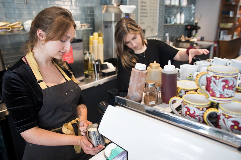 PMG PHOTO: JAIME VALDEZ - Barista Rose Sherman, left, and Elise Stinnett make coffees for customers at Caffe Umbria in downtown Portland. The owner has put wages up in line with the new state minimum, which went to $12.50 in Portland on July, 2019, but is holding back on increasing food and drink prices.  Workers like Sherman at Caffe Umbria usually net around $15 an hour after tips, but the minimum pushes wages up for everyone who works there. THIS PAGE: Susan Thomas, who owns and operates Coffee Time and Cascadia Coffee Pub in Northwest Portland, says minimum wage increases have had no adverse affects for her yet because new apartments and offices have brought in lots of fresh customers.