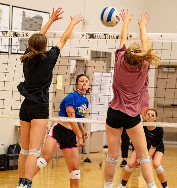 LON AUSTIN/CENTRAL OREGONIAN - Liz Barker hits a ball past the block of Kendall Maycutt and Syrie Ossenkop during the Cowgirls team camp this week. Lily Cooper covers for Barker.