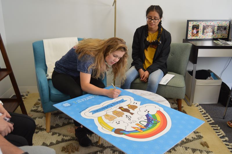 PMG PHOTO: NICOLE THILL-PACHECO - Raleigh Erickson, left, signs an copy of a printed poster that will be on display at the Young Audiences office, the nonprofit that helps run the Run for the Arts design contest.  Grace Brown, right, was a co-designer with Erickson and also autographed the poster.