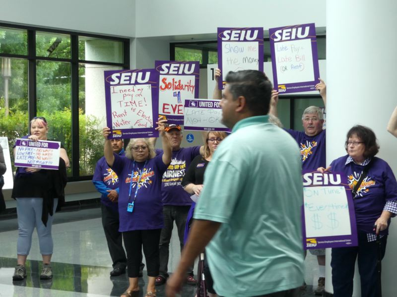 OREGON CAPITAL BUREAU: AUBEY WIEBER - Oregon homecare workers took their protest Thursday, July 18, of late paychecks to the lobby of the state Department of Human Services building in Salem.