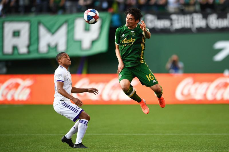 PMG PHOTO: CHRISTOPHER OERTELL - Zarek Valentin (right) heads the ball for the Portland Timbers.