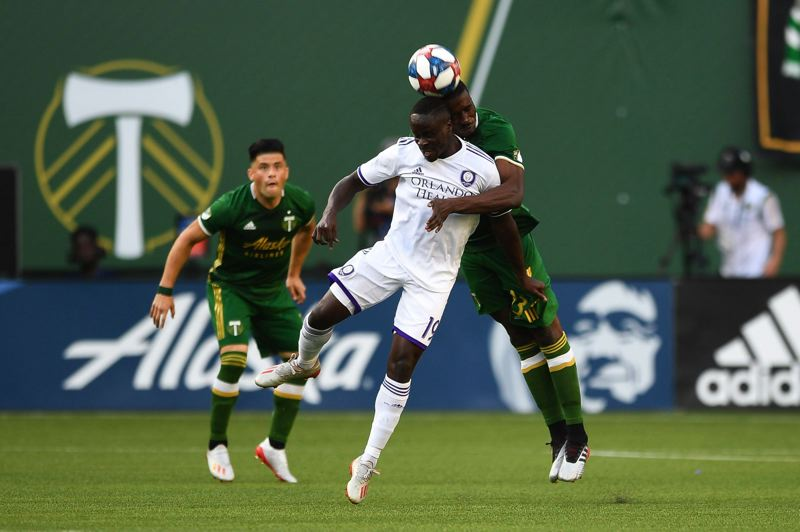 PMG PHOTO: CHRISTOPHER OERTELL - Benji Michel (19) of Orlando City battles for a ball in the air on Thursday night against the Portland Timbers.