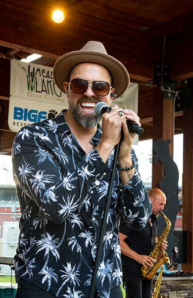 LON AUSTIN/CENTRAL OREGONIAN - Corey Parnell smiles as he sings a song Wednesday at Picnic in the Park. Sax player Andy Warr is in the background.