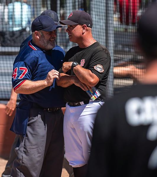 PHOTO COURTESY: HOLLY SPARKS - Sandy coach Ryan Sparks shares a moment with the head umpire during a pool play game on Thursdays opening day at Regionals.