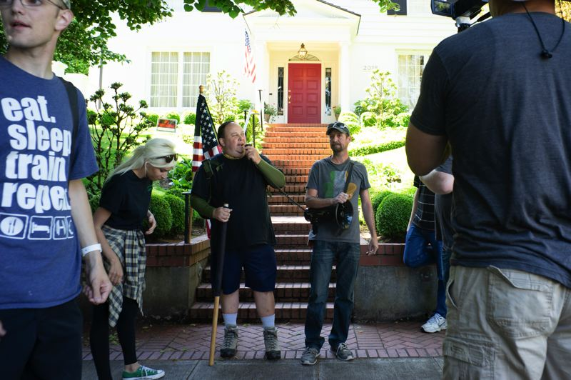 PMG PHOTO: KIT MACAVOY - David Willis (center) speaks to the Portland Liberation group about his frustrations with Mayor Ted Wheeler during a small rally outside the mayor's Southwest Portland home Saturday, July 20.