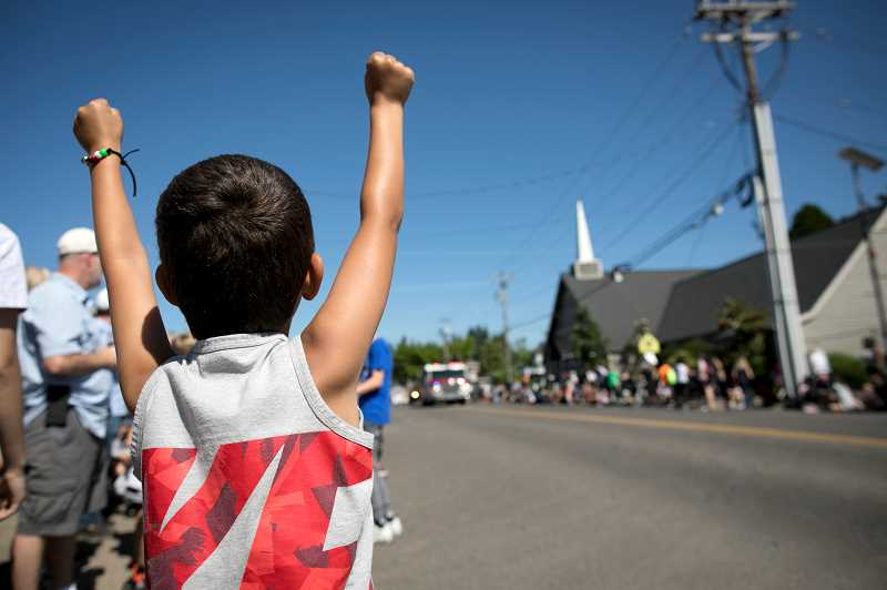 PAMPLIN MEDIA GROUP: JAIME VALDEZ - Espn Esparza,6 , waves to the TVF&R firetruck at the start of the Robin Hood Festival Parade.