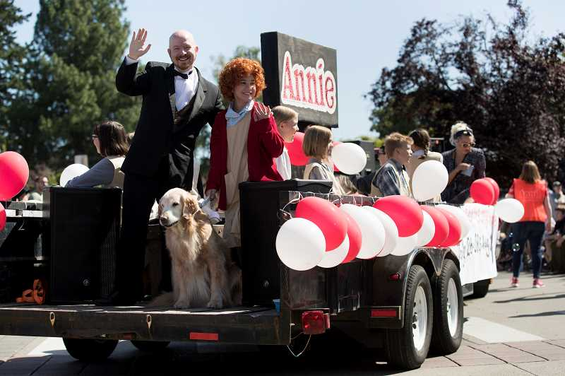 PAMPLIN MEDIA GROUP: JAIME VALDEZ - Cast members from 'Annie,' presented by Sherwood Foundation for the Arts, make their way down Southwest First  Street during the Robin Hood Festival Parade.