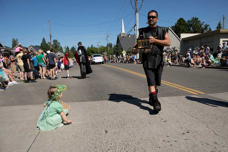 PAMPLIN MEDIA GROUP: RAY PITZ - Jaclyn Hill, 2, watches a man dressed in Medieval garb during the Robin Hood Festival Parade.