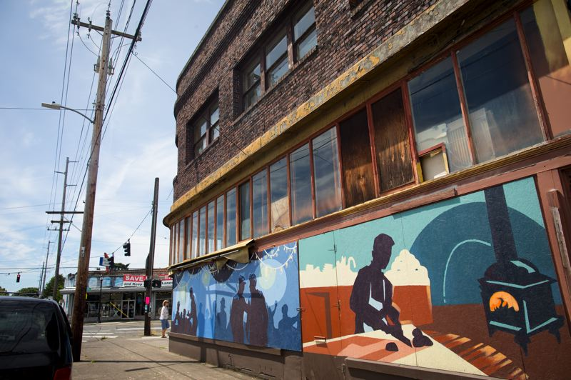 PMG PHOTO: JAIME VALDEZ - The Foster the Phoenix partners have obtained a $20,000 grant from the state to restore the buildings aluminum-and-glass storefront, which currently is covered with murals painted on plywood to discourage vandalism and trespassers.