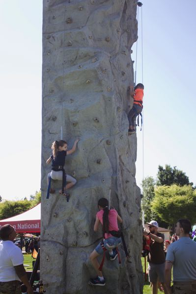 PMG PHOTO: CHRISTOPHER KEIZUR - Adventurous children scaled a rock climbing wall in the Kids Village, dedicated to fun activities for youth at the Gresham Arts Festival.