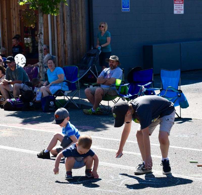PMG PHOTO: MATT DEBOW - Kids decorate the street with chalk before the parade during the Chalk it Up event.