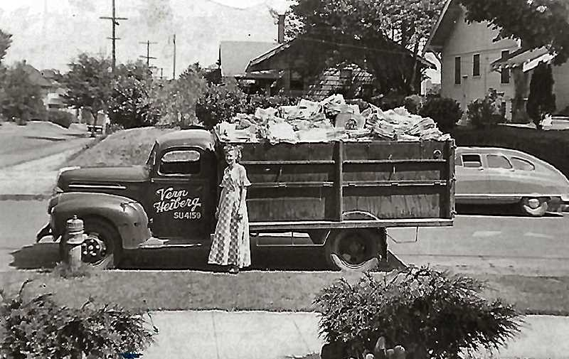 COURTESY OF THE HEIBERG FAMILY - Marian Heiberg stands beside the 1946 V8 Ford  hydraulic garbage truck with side gates, that Vern Heiberg used when he first began operating Heiberg Garbage. Parked in front of their house in Westmoreland, this Heiberg truck is filled with rags collected on the route, ready to be hauled to the recycling depot.