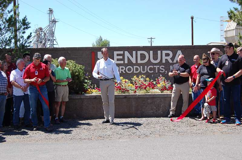 RAMONA MCCALLISTER/CENTRAL OREGONIAN - Kevin MacDonald performs the ribbon cutting in front of the entrance to Endura Products, Inc. on Friday afternoon. The ceremony was to commemorate the final stages of Endura Products' acquisition of Contact Industries, as both organizations will operate under the name of Endura Products, Inc., effective July 16, 2019.