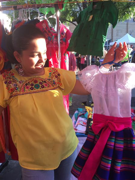 PMG PHOTO BY PETER WONG - Melina Monita displays a girl's dress sewn by her mother at the Ropa Mexicana Monita booth July 20 at Beaverton Night Market