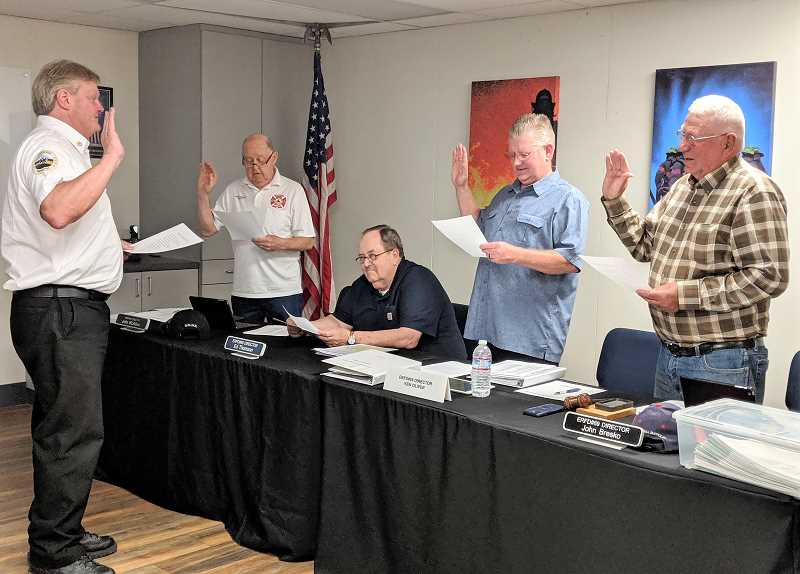 PMG PHOTO: EMILY LINDSTRAND - Members of the Estacada Fire District's board of directors who won election and re-election in May take their oaths of office during a meeting last week.