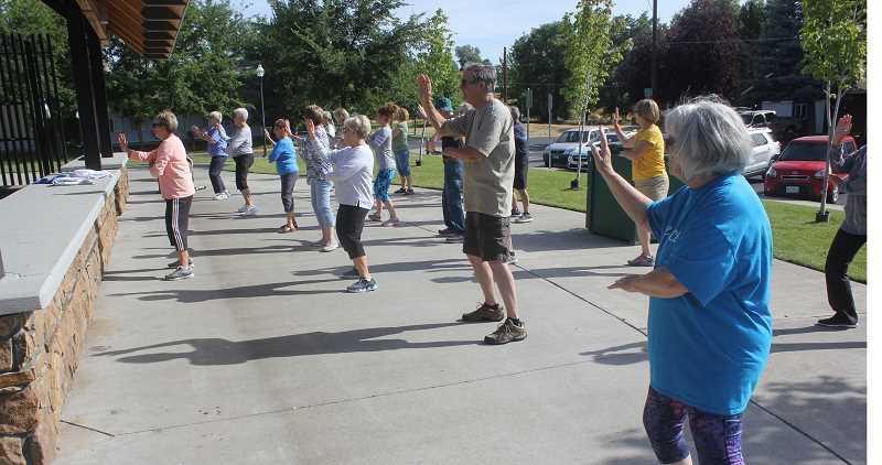 SUSAN MATHENY/MADRAS PIONEER - Madras residents gather in the park for their first outdoor tai chi class.