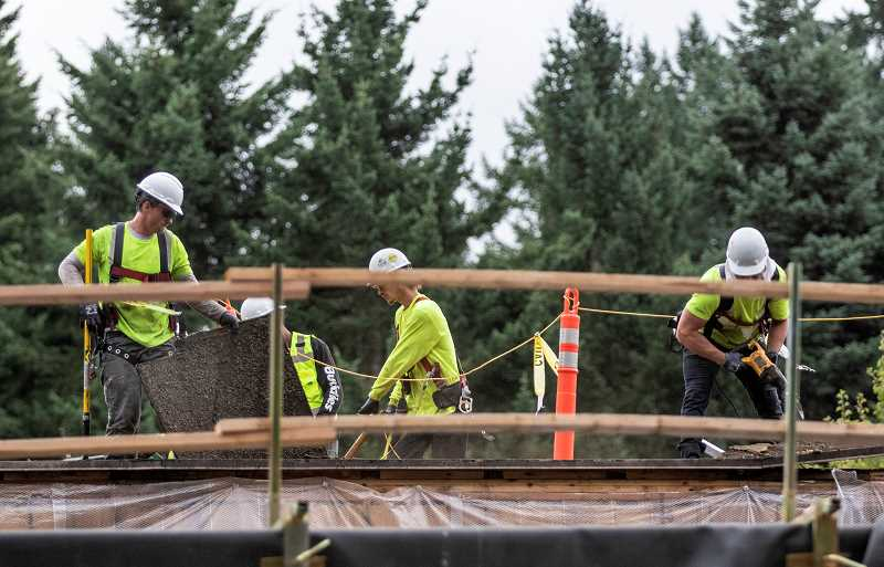 PMG PHOTO: JONATHAN HOUSE - Workers begin the process of replacing the roof on Westridge Elementary School.