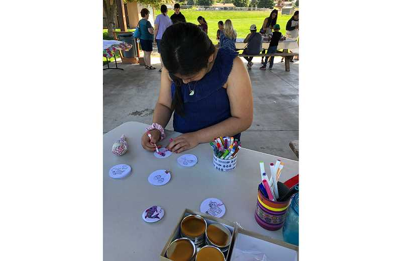 SUBMITTED PHOTO - A participant at the Youth FUN Day at the Culver park last Saturday, colors a design to make a button.