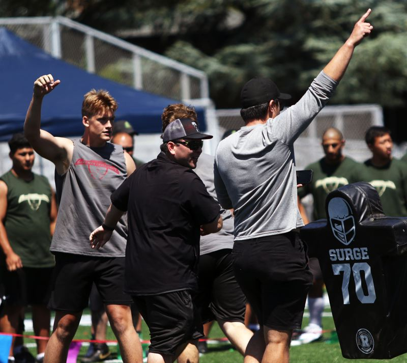 PMG PHOTO: DAN BROOD - Tualatin players and coaches celebrate at the finish of the blocking sled relay at the Metro Area Lineman Challenge.