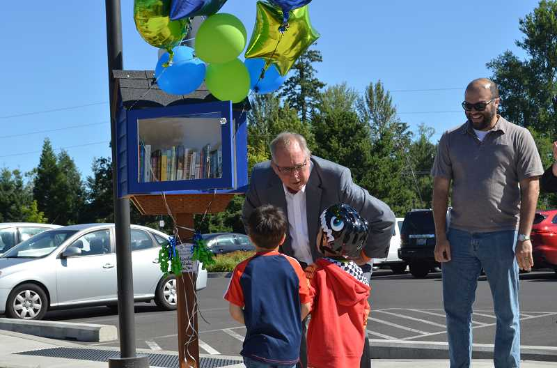 PMG PHOTO: GEOFF PURSINGER - Hillsboro Mayor Steve Callaway talks to two young boys about a new library kiosk at Orenco Woods Nature Park. The kiosks are popping up at several Hillsboro parks as a way to promote reading.