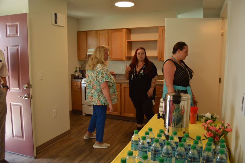 PMG PHOTO: NICOLE THILL-PACHECO - Several people tour one of the apartments at the 18th Street Development during a grand opening ceremony on July 19.  The apartments have a separate bedroom space, a full bathroom, kitchen, living room and closet storage area within the 400-square-foot space.
