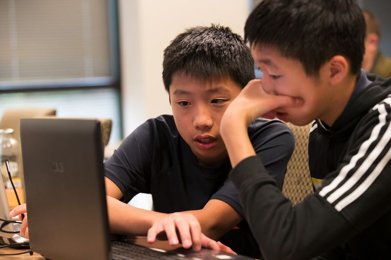 PAMPLIN MEDIA GROUP: JAIME VALDEZ - Twins Maxwell Yang (left) and Alexander, 14, help each other during NW Cyber Camp 2019 at Mentor Graphics in Wilsonville.