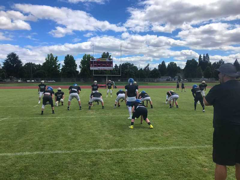 PHOTO COURTESY OF CROOK COUNTY HIGH SCHOOL FOOTBALL - The Crook County High School football team participates in a scrimmage during a team camp at Western Oregon University. Assistant coach Ernie Brooks stands in the foreground. The Cowboys took approximately 40 individuals to the camp, which was held in mid-July, and participated in both varsity and JV competition.