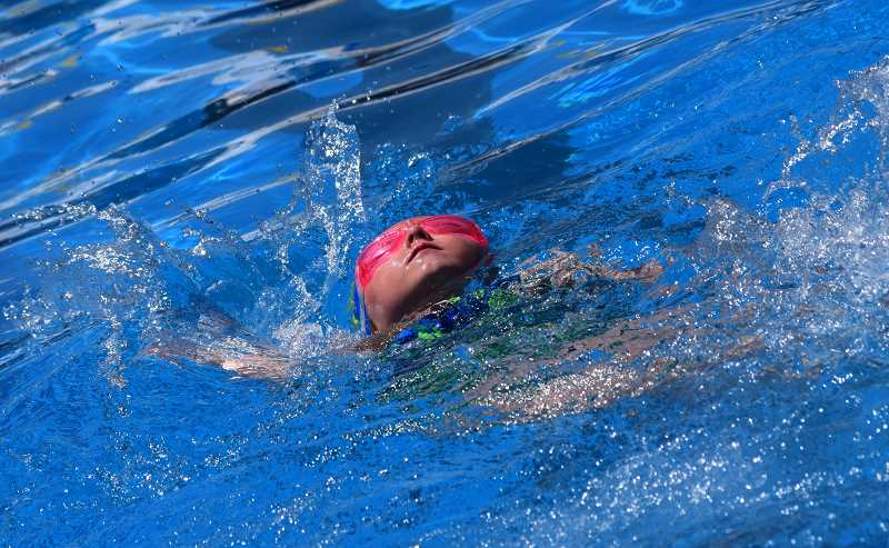 PHOTO COURTESY OF CASSEY DICKEY - Adisynne Hensley swims the backstroke at a meet earlier this year. Hensley will swim in the 8 and under division at the Cascade East District Championships, which will be held this weekend in John Day.