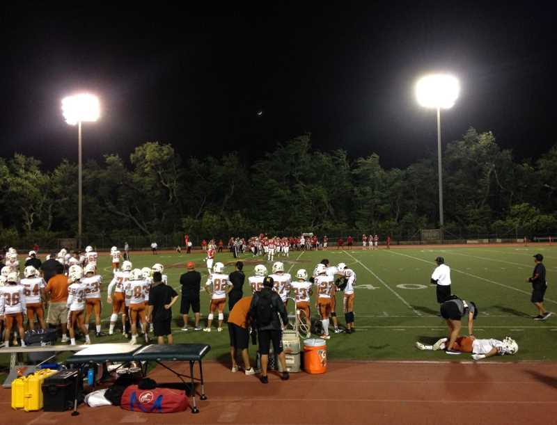 AMANDA WALDROUPE/INVESTIGATEWEST - In Hawaii, where the state funds a pair of athletic trainers at every high school, it's common to see five or more athletic professionals on the sidelines of sporting events.
