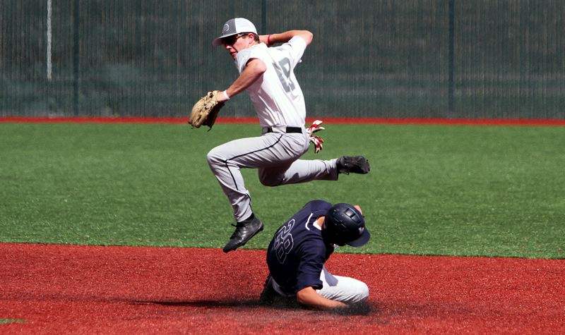 PMG PHOTO: MILES VANCE - Clackamas shortstop Grant Edgerly attempts to turn a double play while Lake Oswego's Casey Graver slides in during the OIBA's National League Tournament semifinals at Tualatin High School om Saturday, July 27.