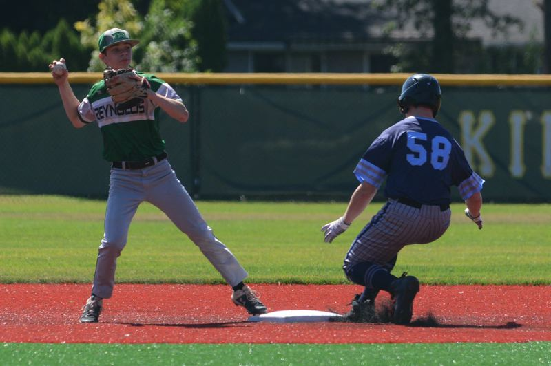 PMG PHOTO: DAVID BALL - Reynolds shortstop Ethan Jerome looks to turn a double play in front of Mt. Hood base runner Phil Morris.