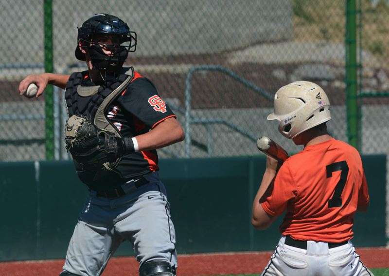 PMG PHOTO: DAVID BALL - Sandy catcher Quinnton Riley looks down the first-base line to challenge a Scappoose runner.