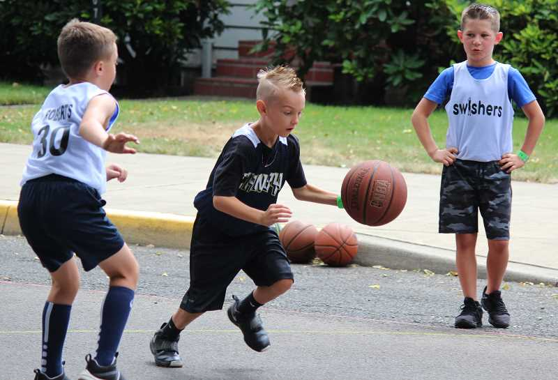 PMG PHOTO: DEREK WILEY - Jeff Shrock driblles around a defender during Canby Rotary's 3-on-3 basketball tournament Saturday at Wait Park.