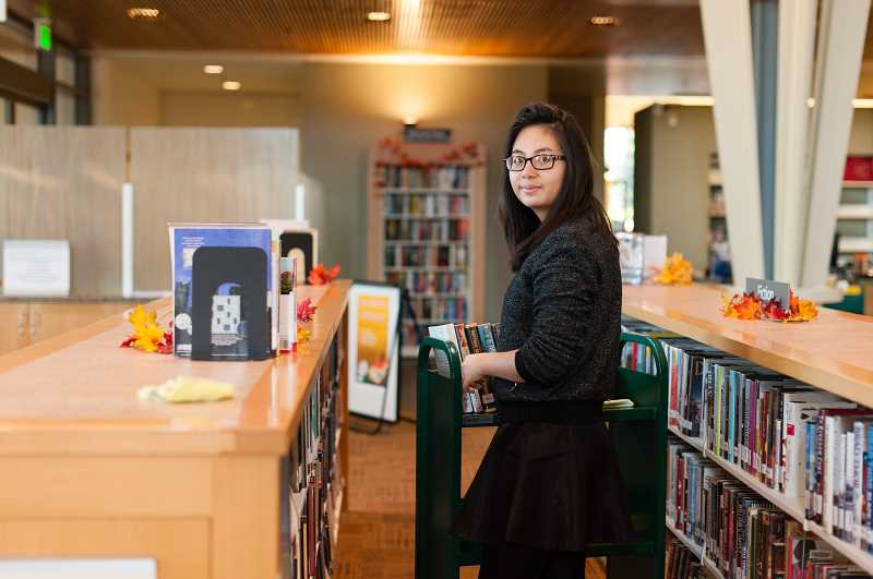 COURTESY OF JENNY SWANSON - Nghi Nguyen volunteered at the Sherwood Public Library throughout high school until she left for college in 2017. Here she helps at a library cleaning party.