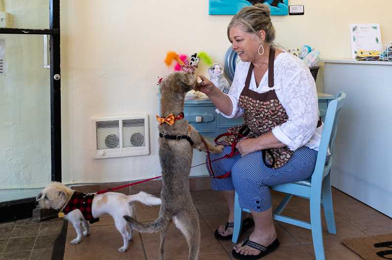 PMG PHOTO: CHRISTOPHER OERTELL - Krystal Monroe feeds her dog Rosie a treat at her Puppernickel dog treat bakery on Third Avenue.