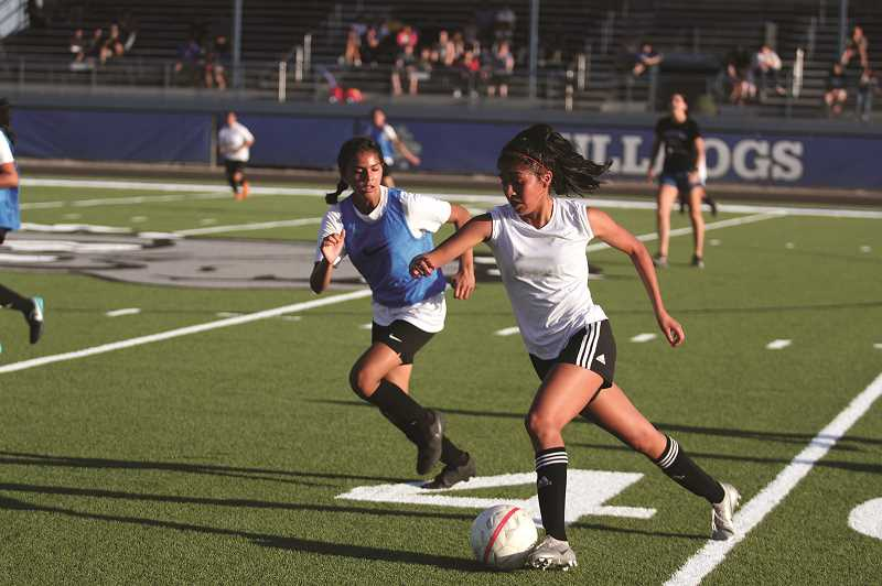 PMG PHOTO: PHIL HAWKINS - The Woodburn girls soccer program made their home field debut on their new synthetic turf last week, playing their final blue vs. white scrimmage on July 24.