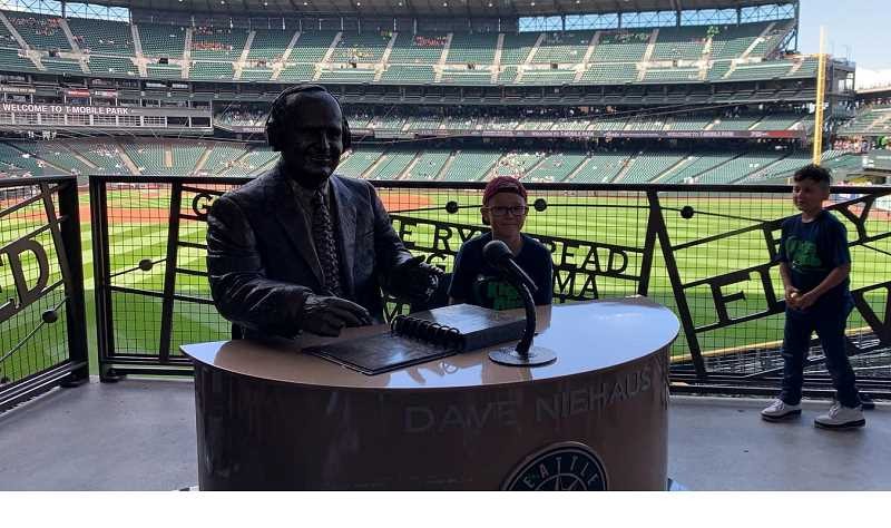 SUBMITTED PHOTO - Merrick Towers sits by a statue of Dave Niehaus, a famous announcer, who was the voice of the Mariners from 1977 until 2010, when he passed away.