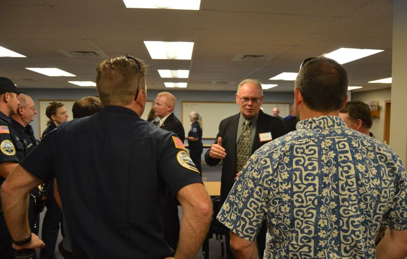 PMG PHOTO: NICOLE THILL-PACHECO - Dennis Hoke, center, speaks with visitors at a meet-and-greet event on Sunday, July 28. Hoke was selected the Scappoose Fire District and Columbia River Fire and Rescue boards of directors as the new fire chief after final interviews on Monday, July 29.