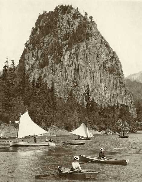 PHOTO AND RESEARCH BY JOHN KLATT, OLD OREGON PHOTOS - Boating at Castle Rock, circa 1901: Two properly attired women manage their rowboats in the foreground of this idyllic scene at Castle Rock, now known as Beacon Rock, on the Columbia River.  At about this time, in 1901, the rock was scaled for the first time, by climbers who left spikes and ropes in place for others who followed.  In 1904 the rock was purchased by Charles Ladd, who essentially saved it for future generations, as there were plans to blast it and use pieces to create a jetty at the mouth of the Columbia.