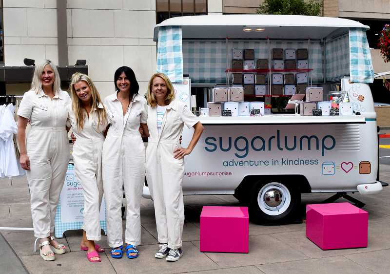 PMG PHOTOS: GABBY REMINGTON  - From left, Erin Sorenson, Beret Dahms, Nicole Selis and Heather Gardella pose by the Sugarlump Dub Box, which is their mobile shop for Sugarlump kits, T-shirts and more. The women invite all to join their adventure in kindness.