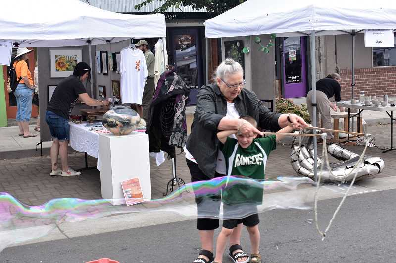 PMG PHOTO: EMILY LINDSTRAND - Annette Reisbick helped interested participants create giant bubbles during the Estacada Summer Celebration on Saturday, July 27.