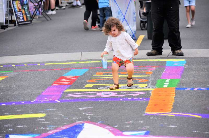 PMG PHOTO: EMILY LINDSTRAND - A young Summer Celebration attendee navigates through the labyrinth on Third Avenue and Broadway Street.