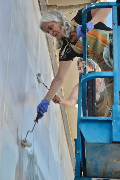 PMG PHOTO: BRITTANY ALLEN - Artists and Arts Commissioners Pamela Smithsted and Becky Hawley work to seal in remaining details of Roger Cooke mural.