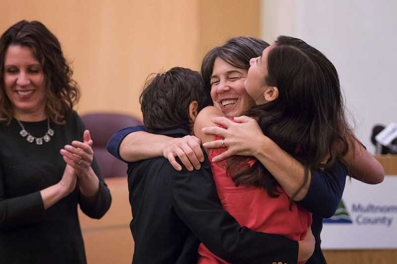 PMG PHOTO: JONATHAN HOUSE - Multnomah County Commissioner Sharon Meieran gets hugs from her son Ben and daughter Ella after being sworn into office in January 2017. County Chair Deborah Kafoury, who she replaced as District One Commissioner, stands to the left.