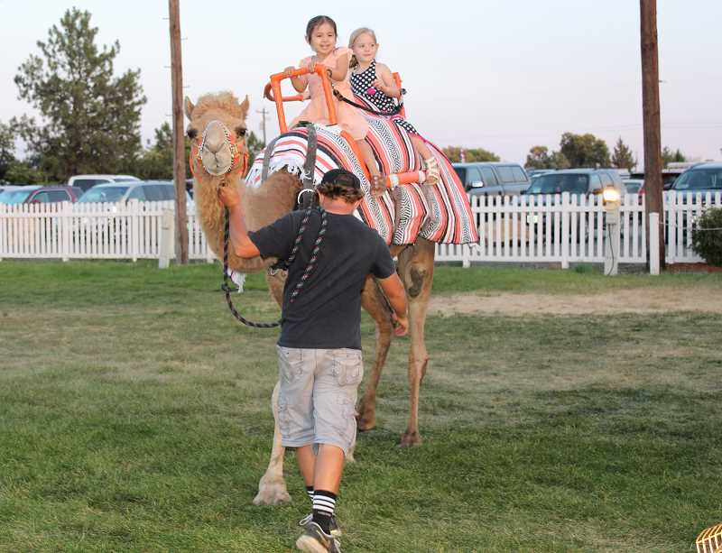 HOLLY M. GILL/ MADRAS PIONEER - Rosie Lockwood, 5, and Amber Wolfe, 3, of Madras, get a ride on a camel Friday night, just before dusk, at the fair.