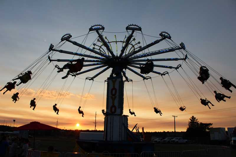 TONY AHERN/MADRAS PIONEER - A packed Yo-Yo swings riders around against a beautiful sunset at the 2019 Jefferson County Fair and Rodeo, which featured rides from Davis Amusement.