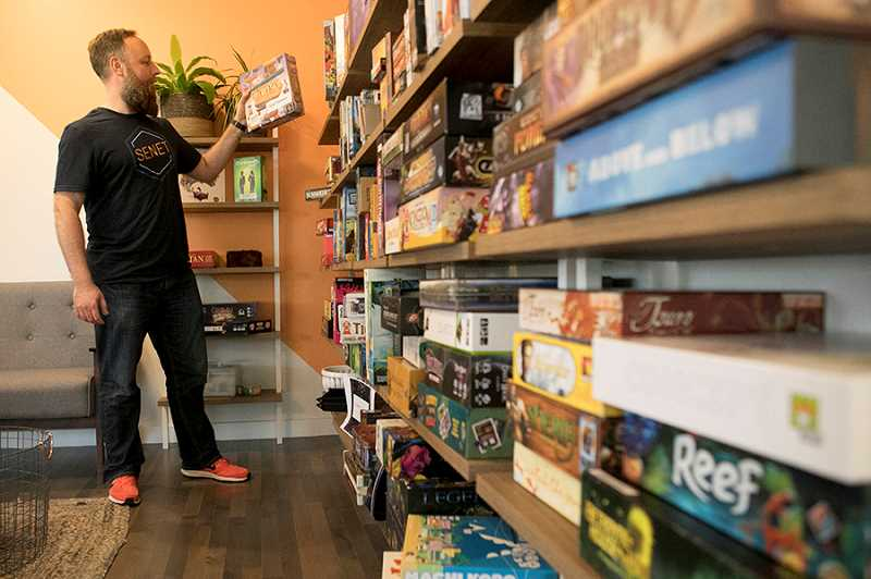 TIMES PHOTO: JAIME VALDEZ - Derrick Wright shows off the dozens and dozens of games that line the walls of his Senet Game Bar in Downtown Tigard.