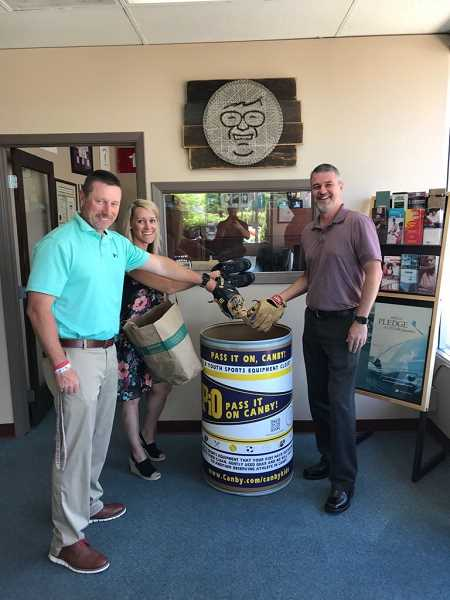 COURTESY PHOTO: OLIVER INSURANCE - From left to right, Ryan Oliver, Summer Buel and Kent Petterson show off Oliver Insurance's 'Pass it On, Canby!' bin for collecting gently-used sports equipment.