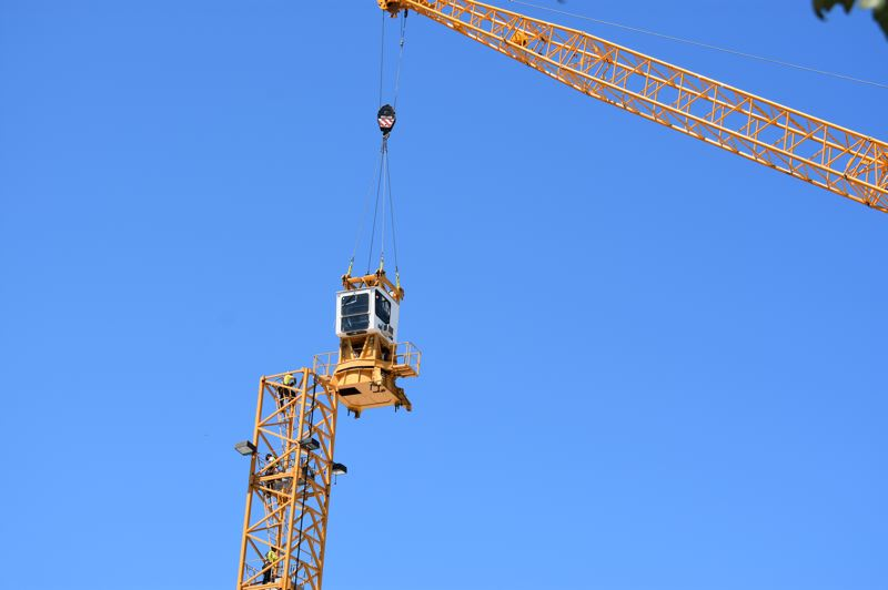 PMG PHOTO: TERESA CARSON - A mobile crane lifts the operators cab off the giant tower crane.